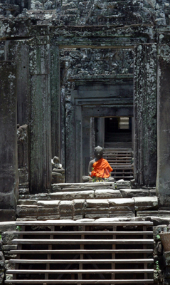 A saffron-robed Buddha statue in a temple gateway