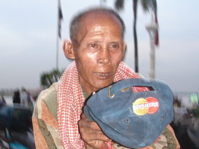 A Cambodian beggar holds out a cap with the MasterCard logo