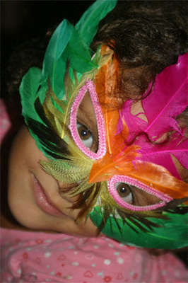 A young girl wearing a brightly coloured mask gazes into the camera