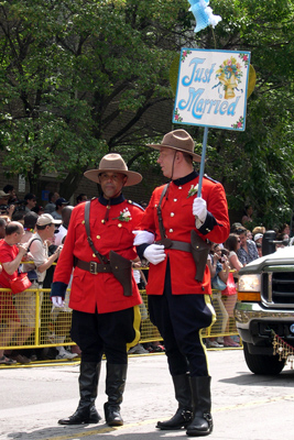 Two men in Mountie uniforms in a gay pride parade, one holding a 'Just Married' sign