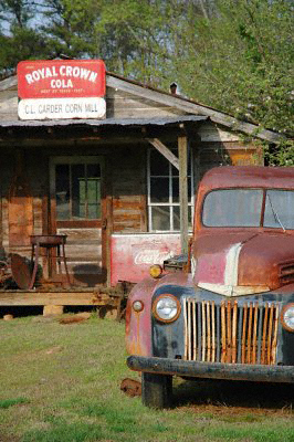 An ancient and rusty pick-up outside an old corn mill