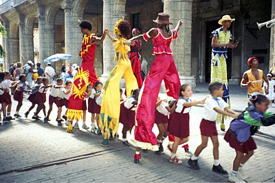 Cuban children in Young Pioneer uniforms dance the conga between the legs of carnival characters on stilts