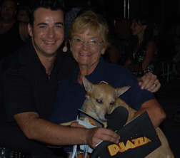 Dennis, a small brown dog, held by Betty from Gozo SPCA, with a Maltese TV presenter