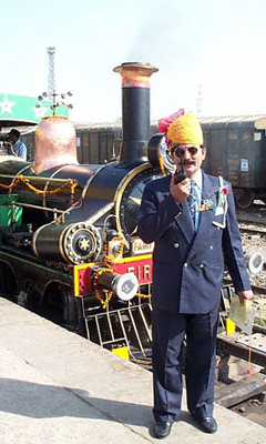 An Indian Railways official with a brightly coloured Rajasthani head-dress stands by the Fairy Queen steam locomotive