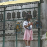 A little girl stands next to some prayer wheels in a Kathmandu courtyard