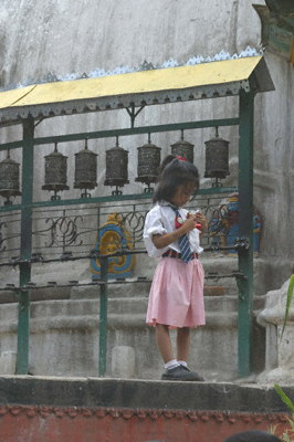 A little girl stands next to some prayer wheels in a Kathmandu courtyard