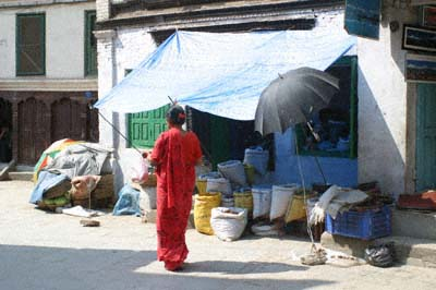 A woman in red walks past a shop front in Kathmandu