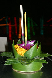 A krathong - made of a slice of banana stem, banana leaves, flowers, joss sticks and a candle