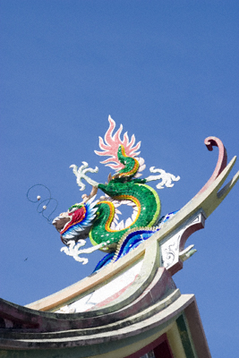 A brightly coloured Chinese dragon on a rooftop against a blue sky