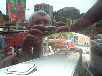 Photograph taken from an open-top bus - the head and shoulders of the photographer appear reflected above the archway on the road ahead