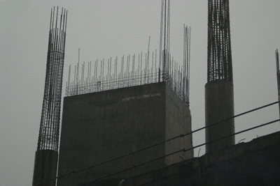 An unfinished concrete building against a thundery Bangkok sky