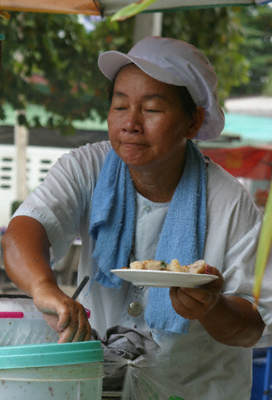 A Thai food hawker prepares rice cakes for a customer