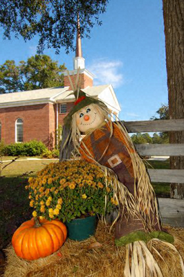 A Thanksgiving display (scarecrow, flowers and a pumpkin) outside a church in Springfield, Georgia, USA
