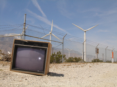 An abandoned television set outside a fenced-off wind farm