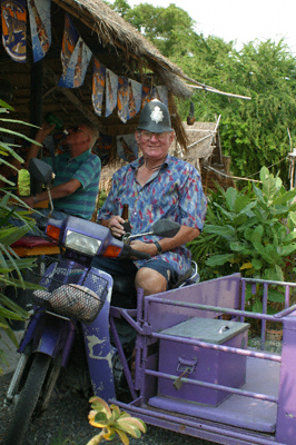 Walter sitting on a purple scooter and sidecar and wearing a toy British policeman's helmet