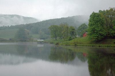 A farmhouse by a lake in the rain