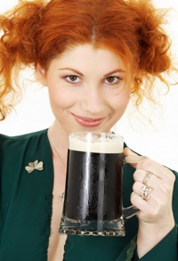 A flame-haired young woman enjoys a Guinness