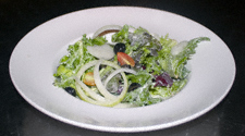 A freshly dressed leafy salad with onion, cherry tomatoes and black olives