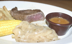 Cold (and undercooked) steak, frozen fries, watery peppercorn sauce (no peppercorns in evidence), pale, greasy onions and corn-on-the-cob on a plate