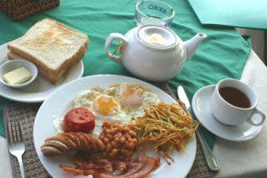 A full English breakfast - bacon, fried egg, sausage, beans, tomato, hash browns, toast and tea