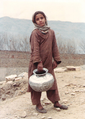 A girl in Pakistan's North West Frontier Province, carrying a steel water pot