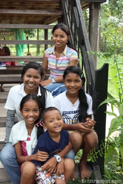 Happy Cambodian children sitting on wooden steps