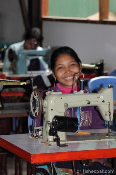 A smiling young Cambodian woman at a sewing machine