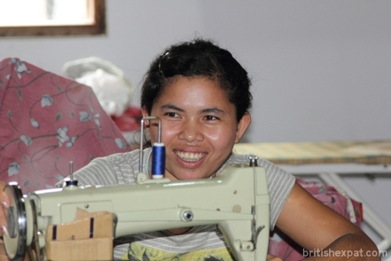 A smiling young Cambodian girl operating a sewing machine