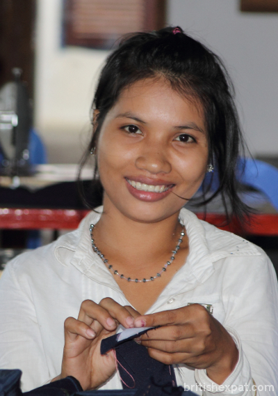 A smiling young Cambodian woman with some sewing work
