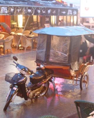 A tuk-tuk caught in torrential rain in Siem Reap's Pub Street