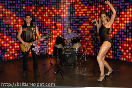 Waxworks of a Thai rock star and Beyoncé Knowles, with Kay sitting behind the drums