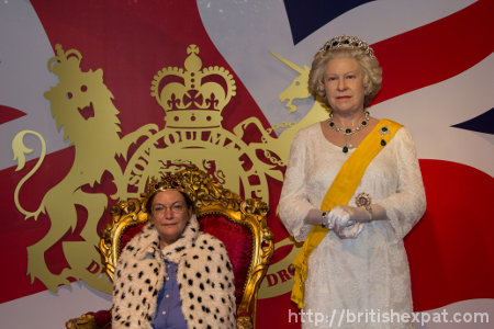 Kay, wearing fake ermine and plastic crown, sits in a throne beside a waxwork of Queen Elizabeth II at Madame Tussauds in Bangkok