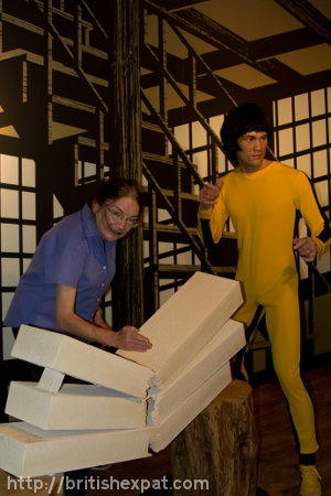 Kay chops concrete blocks with her bare hands in front of a waxwork of Bruce Lee