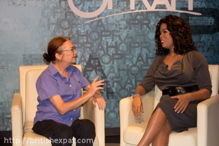 Kay sits in an interview chair beside a waxwork of Oprah Winfrey
