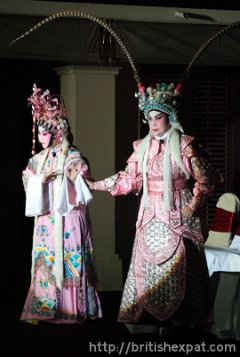 Two Cantonese opera singers perform a duet in the spotlight