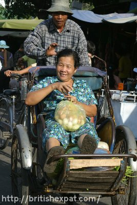A Cambodian cyclo and its passenger trundle through a busy market