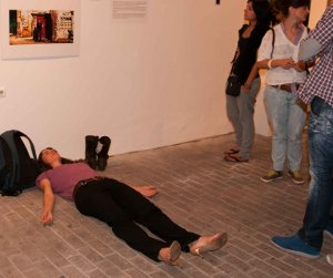 A performance artist lies in the middle of the floor, creating an obstacle