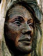 A tattooed face carved into a tree trunk by a Maori artist