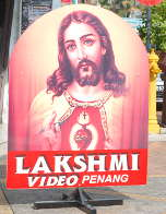 Sign outside the Lakshmi video shop in Penang, with a rather incongruous Bleeding Heart Jesus