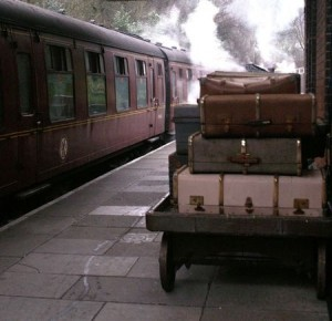 Luggage and a steam train in a station