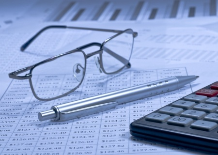 Financial spreadsheets with a calculator, pen and spectacles