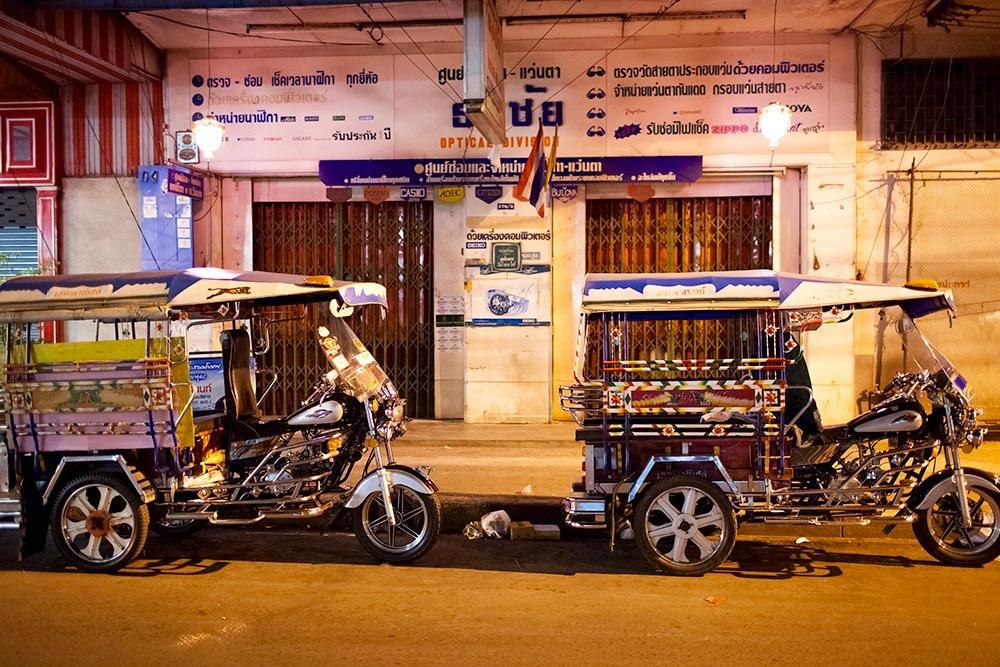 Two tuk-tuks outside a shopfront in Bangkok
