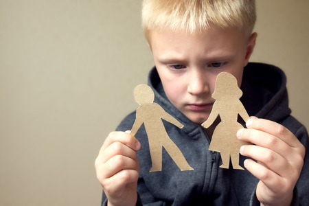 Tug of love - a child frowns while holding card cut-outs of a man and a woman