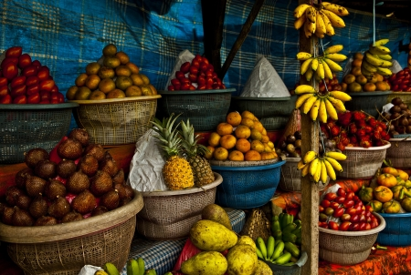 photo of finger bananas, pineapples, rambutans, persimmons and other tropical fruit on a market stall in Bali