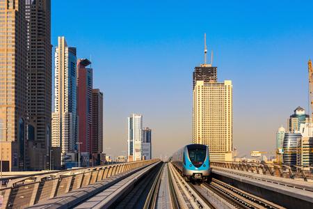 A metro train leaves a station in Dubai
