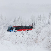 A funicular tram in a snowy mountain forest